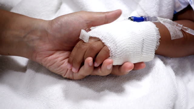 Close up of young parent and sick little daughter holding bandaged hands for comfort in a hospital bed video
