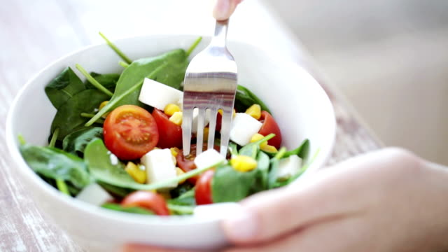 close up of young woman eating salad at home healthy eating, dieting and people concept - close up of young woman eating vegetable salad at home fork stock videos & royalty-free footage