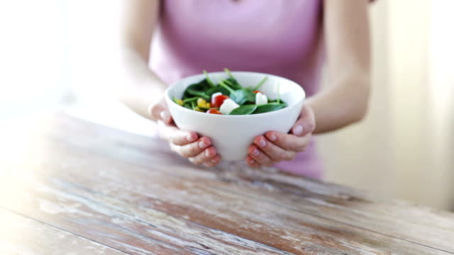 close up of young woman hands showing salad bowl healthy eating, dieting and people concept - close up of young woman hands showing salad bowl at home salad bowl stock videos & royalty-free footage