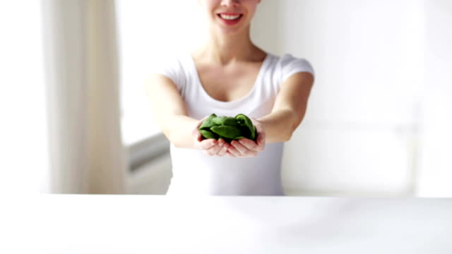 close up of young woman showing spinach healthy eating, dieting, vegetarian food and people concept - close up of young woman showing spinach at home handful stock videos & royalty-free footage