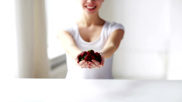 close up of young woman showing strawberries healthy eating, dieting, vegetarian food and people concept - close up of young woman showing strawberries at home handful stock videos & royalty-free footage