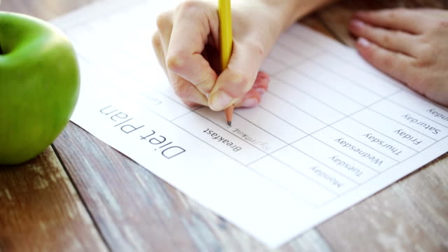 close up of young woman writing diet plan at home - progettare video stock e b–roll