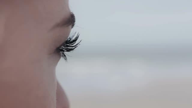 若い女性のクローズアップの目に孤独なビーチ。 - 人の肌点の映像素材/bロール