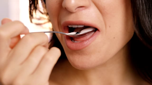 Close up on a brown woman eating a yoghurt video