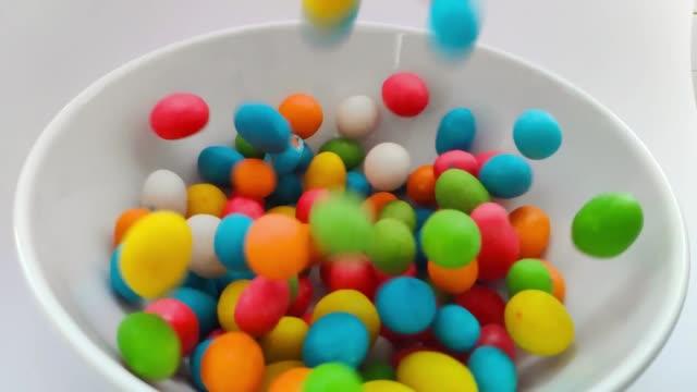 закройте падающие сладости. красочный сладкий фон конфеты. - white background стоковые видео и кадры b-roll