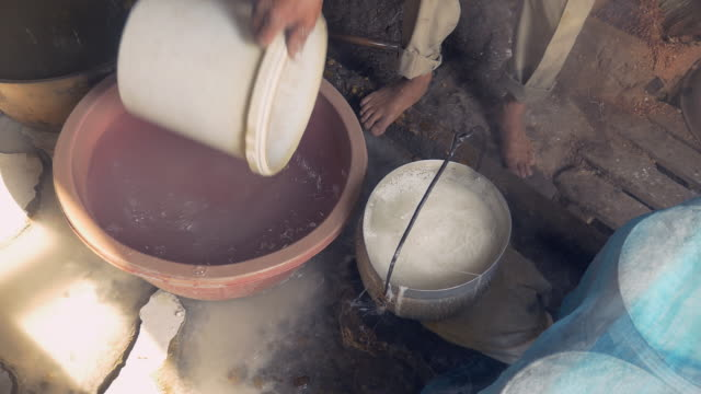 Close up on a man softening rice noodles with water in a holed bucket Close up on a man softening rice noodles with water in a holed bucket household fixture stock videos & royalty-free footage