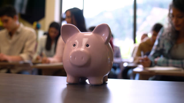 close up on a pink piggy bank and students at the background studying - frugal lifestyle stock videos and b-roll footage