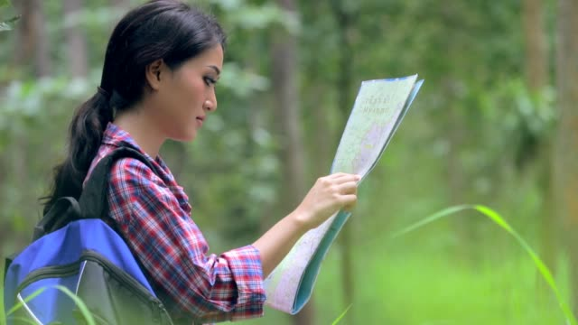 地図、スローモーションを見て若いアジア女性エクスプ ローラーにクローズ アップ - 自然旅行点の映像素材/bロール