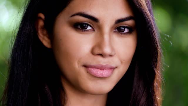Cierre de Asia hermosa mujer dar vuelta hacia la cámara y sonriendo suavemente - vídeo