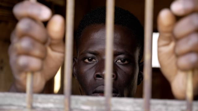 close up on Black african man alone behind bars. refugees, imprisonment, pain