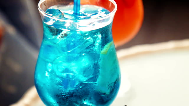 Close up on blue beverage with fruit slice Close up on icy cold blue beverage with fruit slice and matching straw with copy space curaçao stock videos & royalty-free footage