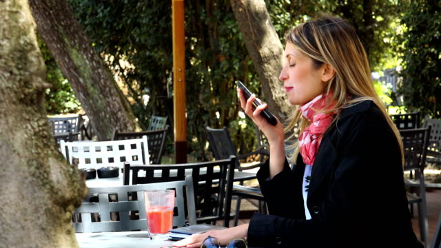 Close up on business Woman Talking On Smartphone with speakerphone- outdoor video