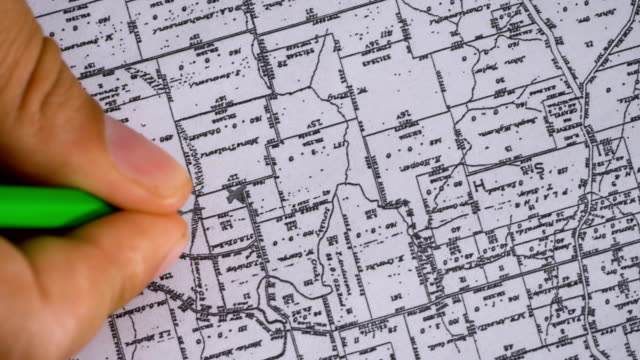 close up on  Businessman hand marks a site with a pencil on a map video