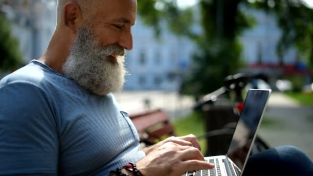 Close up on cheerful mature guy typing outdoors video