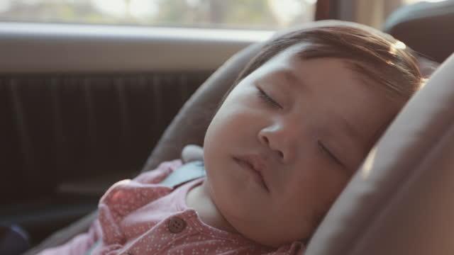 スローモーションショットで家族と一緒に旅行しながら、車の座席に座って眠っているかわいいアジアの幼児の女の子にクローズアップ。 - 安全点の映像素材/bロール