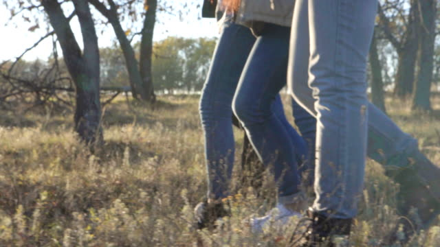 Close up on feet walking opposite the sun in field video