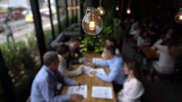 Close up on foreground of a lightbulb while business people are in a meeting