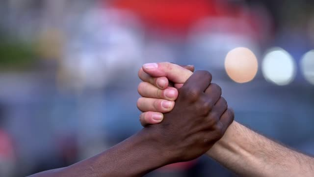close up on friendship, interracial, brotherhood. black and white man hand shake - rispetto video stock e b–roll