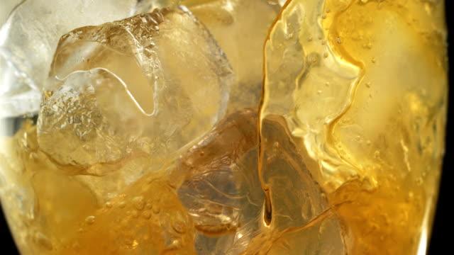 vídeos de stock e filmes b-roll de close up on glass full of yellow carbonated drink - bebida fresca