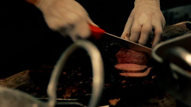 vídeos de stock e filmes b-roll de close up on hands holding a smoked brisket on a cutting board and quickly slicing cooked beef meat into thin slices for a barbecue plate in a restaurant - burned cooking
