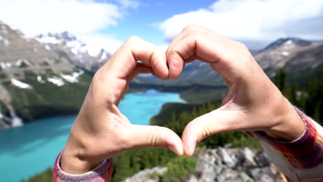 Close up on hands making heart shape frame on mountain lake landscape video