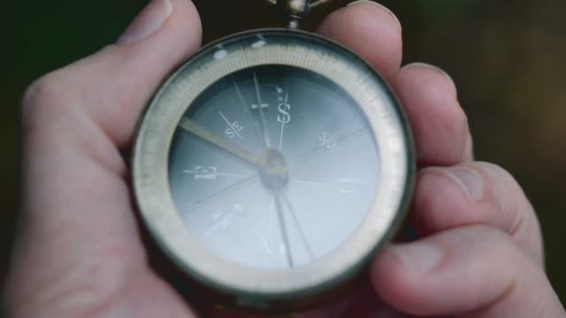 Close up on old compass instrument in hand. shot in slow motion