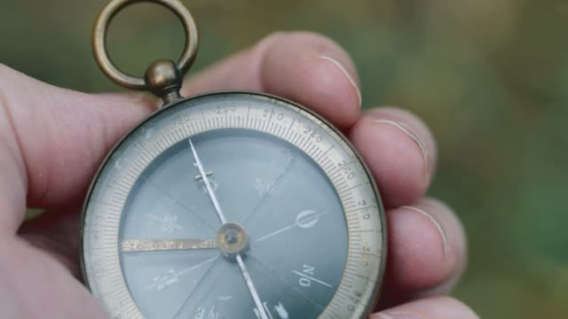 Close up on old compass instrument in hand. shot in slow motion Close up on old compass instrument in hand. shot in slow motion navigational compass stock videos & royalty-free footage