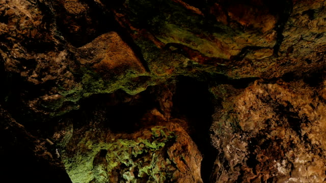 close up on rock wall in a  big cave- cuevas de los verdes, lanzarote - кейвинг стоковые видео и кадры b-roll