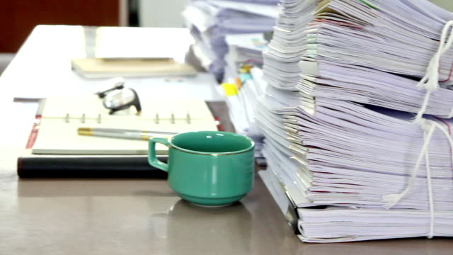 Close up on stack of documents on desk in office video