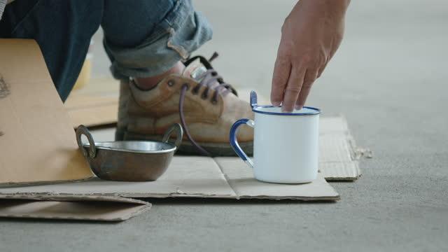 крупным планом на чашку бездомного, который люди дают монеты деньги - голодный стоковые видео и кадры b-roll