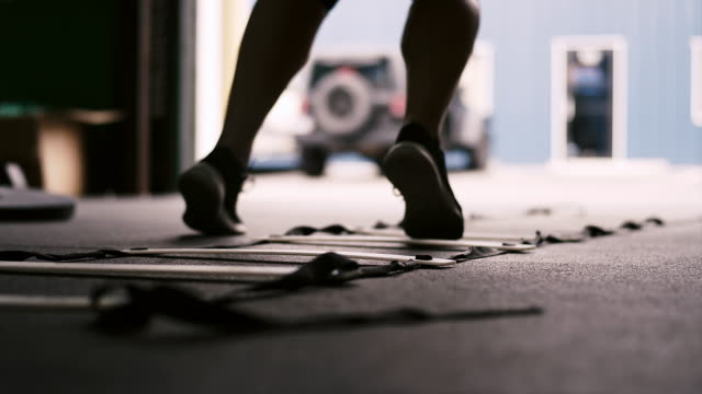 Close up on the feet of a person running a ladder drill at a small gym video