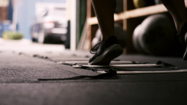 Close up on the feet of a person running a ladder drill at a small gym Close up on the feet of a person running a ladder drill at a small gym cross training stock videos & royalty-free footage