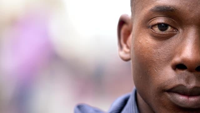 stockvideo's en b-roll-footage met close-up op jonge zwarte afrikaanse man staren camera buiten-half gezicht - portait background
