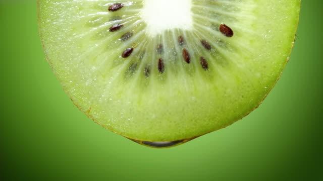 närbild eller makro av en skiva kiwi, en droppe vatten faller i slow motion. - kiwifrukt bildbanksvideor och videomaterial från bakom kulisserna