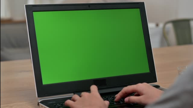 Close up over shoulder view of woman using notebook computer with green screen on the table.