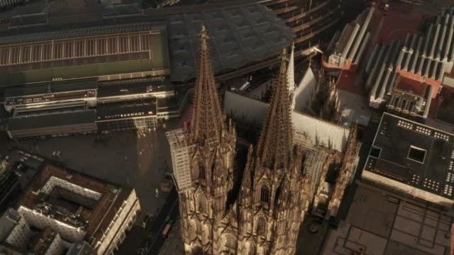 aerial: close up overhead shot des kölner doms zwei braune türme im schönen sonnenlicht [4k] - köln stock-videos und b-roll-filmmaterial