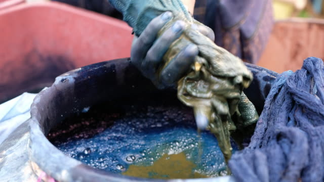 vídeos de stock e filmes b-roll de close up people doing mud indigo dyed cotton handmade in thailand. - matéria corante