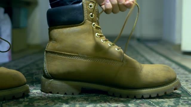人関係をブーツの靴ひもを古典的な暖かい冬を閉じる - 結ぶ点の映像素材/bロール