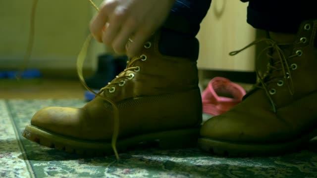 vidéos et rushes de gros plan des liens de personne lacets classique chaud d'hiver des bottes - bottes