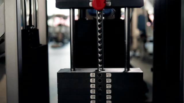 vídeos de stock e filmes b-roll de close up plate stacked of weight machine with kilogram and pound number at fitness gym macro super closeup - aparelho de musculação