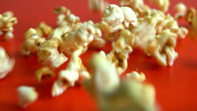 close up popcorn falling on red floor.  slow motion. closeup. fresh fluffy popcorn falling on authentic red table. - gotowy do jedzenia filmów i materiałów b-roll
