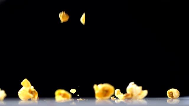 vídeos de stock, filmes e b-roll de close-up pipoca caindo no chão branco, fundo preto, câmera lenta. - junk food