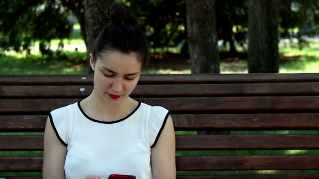 close up portrait a beautiful young girl in a white t-shirt is chatting in social networks on her smartphone while sitting on a bench in a park. - maglietta bianca video stock e b–roll