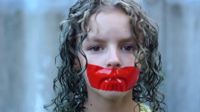 vídeos de stock, filmes e b-roll de feche acima do retrato de uma menina triste curly do adolescente com sua boca gravada sobre com fita vermelha. violação da liberdade de expressão e conceito de censura - domínio