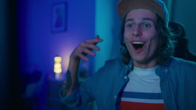 close up portrait of a handsome excited young man watching an action video on a computer. he has long hair and blue eyes. screen adds reflections to his face. cozy room is lit with neon light. - sorpresa video stock e b–roll