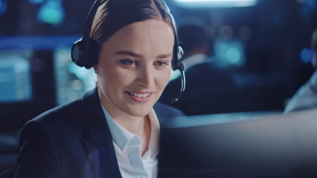 close up portrait of a happy beautiful technical customer support specialist talking on a headset while working on a computer in a dark monitoring room filled with colleagues and display screens. - call center стоковые видео и кадры b-roll