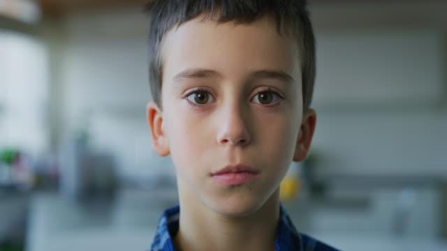 närbild porträtt av en liten pojke med bruna ögon tittar i kameran på köks bakgrund. - barn bildbanksvideor och videomaterial från bakom kulisserna