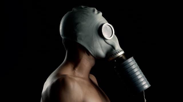 防毒マスクで裸の男の肖像画を間近します。 - こっそり点の映像素材/bロール