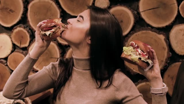 Close up portrait of a smiling hungry young woman eating burger Close up portrait of a smiling hungry young woman eating burger bacon stock videos & royalty-free footage