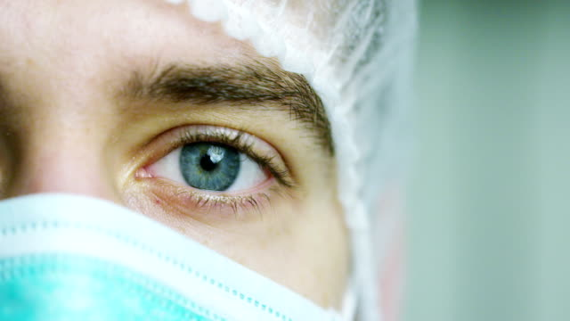 close up portrait of a surgeon or doctor with mask and headset ready for operation in hospital or clinic. the surgeon smiles safe and proud of himself. - mask стоковые видео и кадры b-roll